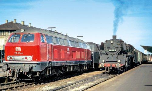 Da ist die neue Lok, leuchtend rot: 215 112 ist am 18. Oktober 1970 in Aalen einer planmäßigen 50er vorgespannt. Mit dem Personenzug 3440 soll es nach Schorndorf gehen, und auf der 215 wird Personal geschult. Noch hat die 003 276 mit dem P 3530 von...