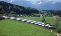 Blau und weiß, Bayern in Reinkultur: Westlich von Axdorf reicht der Blick über Vachendorf hinweg bis zum Hochfelln und Hochgern. Davor kommt im Mai 1995 der InterRegio 2191 Karlsruhe – Salzburg, gezogen von 111 194, vorüber