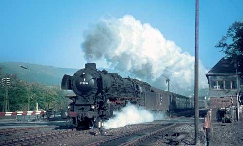 Die 01 1084 ist am 23. Oktober 1965 auf der oberen Ruhrtal-Bahn Hagen – Bestwig – Warburg unterwegs und passiert mit dem langen E 442 am Haken den Bahnhof Oeventrop. Helmut Dahlhaus