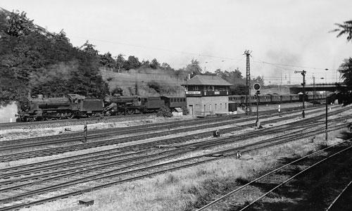 Was für eine Performance: Die 38 3003 leistet der 18 102 Vorspann vor dem Personenzug 1847. Dessen Länge zeigt, warum das nötig ist (Stuttgart Nord am 8. Juli 1949)                   Carl Bellingrodt/Slg. H. Brinker